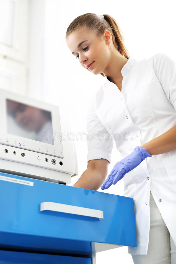 A nurse prepares an injection. A nurse at the doctor's office opens a drawer stock photography
