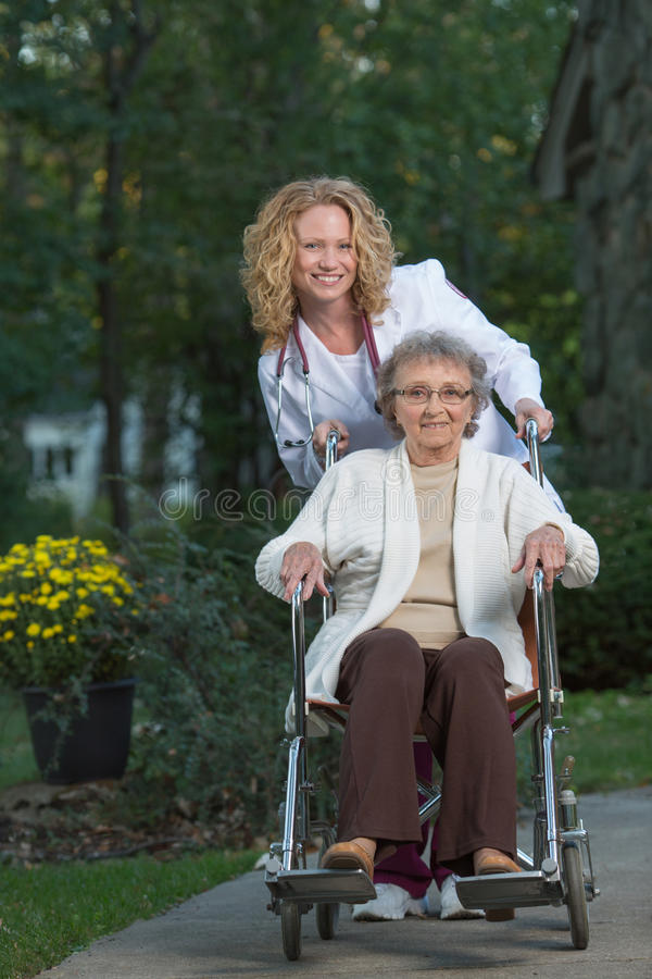 Nurse Push Senior On Wheelchair Outdoor Royalty Free Stock Image