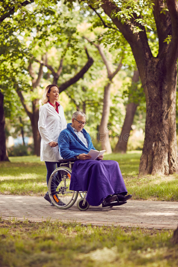 Nurse pushing elderly man in wheelchair while reading book stock photo