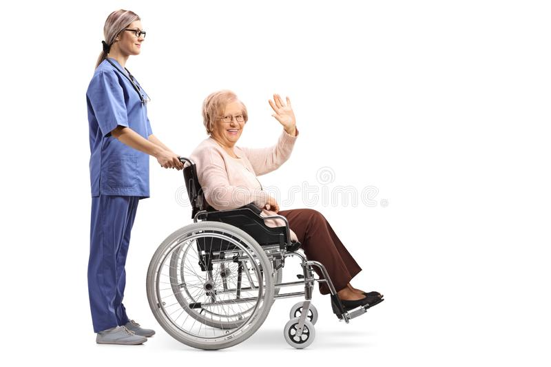 Nurse pushing a senior woman in a wheelchair waving royalty free stock image