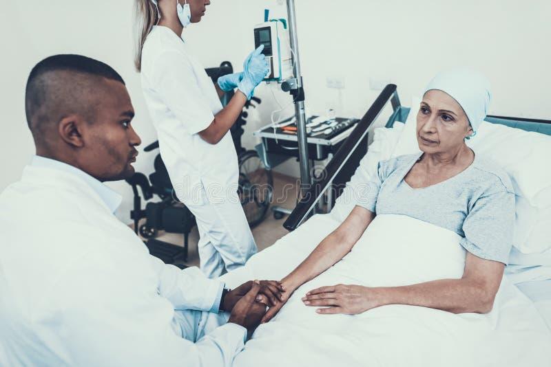 Nurse Puts Dropper. Doctor Holding Patient`s Hand. stock images