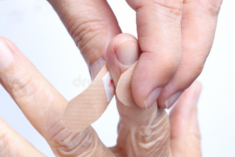 Nurse putting adhesive bandage on elderly hand. Nurse putting adhesive bandage on elderly women hand royalty free stock photo