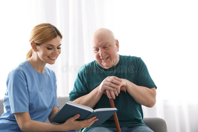 Nurse reading book to elderly man. Assisting senior people royalty free stock photo