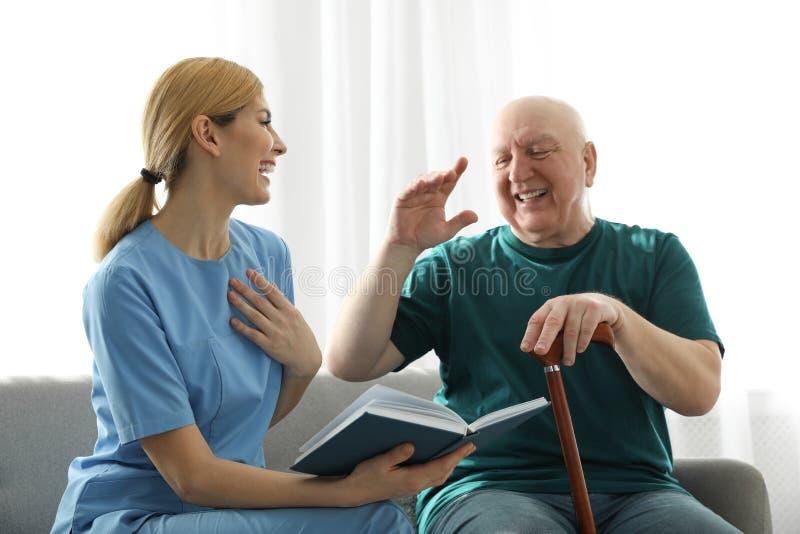 Nurse reading book to elderly man. Assisting senior people royalty free stock image