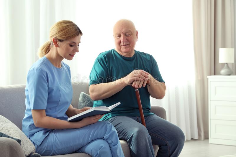 Nurse reading book to elderly man. Assisting senior people royalty free stock images