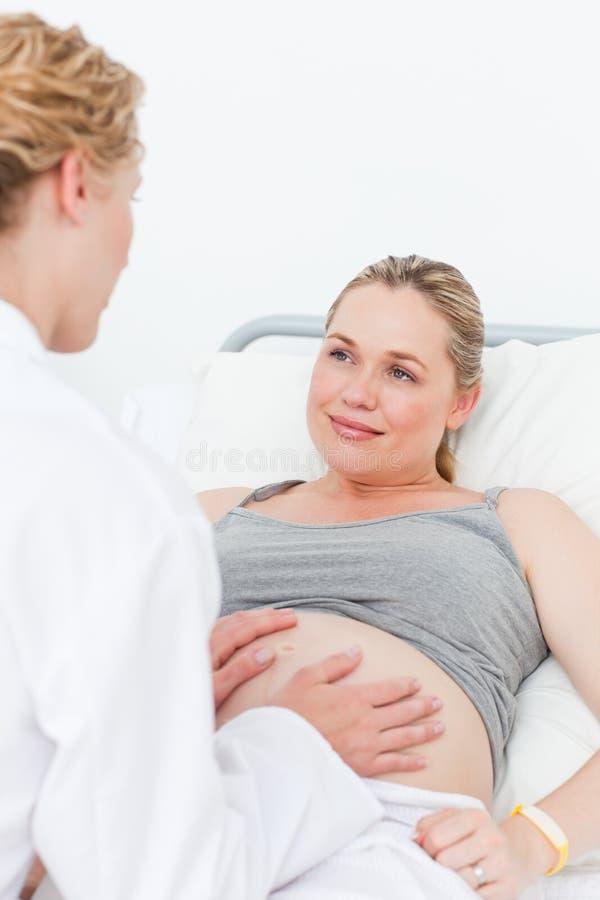 Nurse reassuring her pregnant patient stock image