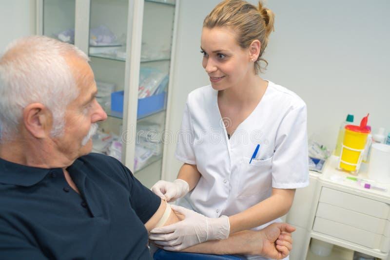 Nurse releasing tourniquet from patients arm stock photos