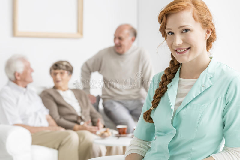Nurse at retirement home. Smiled nurse at retirement home with seniors stock photo