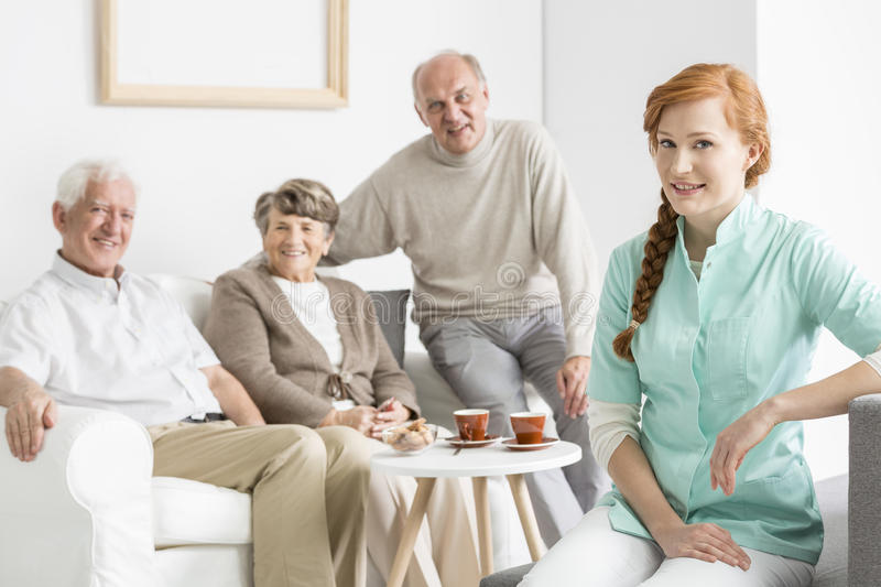 Nurse with senior charges. Young nurse with senior charges on a couch royalty free stock photos