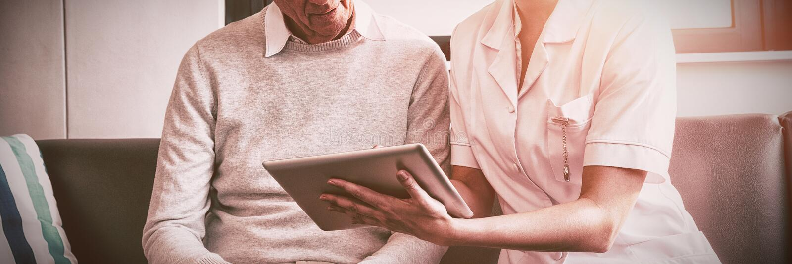 Nurse and senior man using a digital tablet royalty free stock photography
