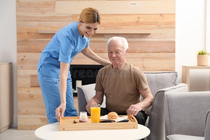 Nurse serving breakfast to elderly man indoors stock images