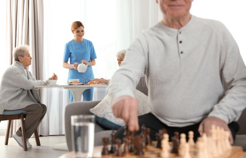 Nurse serving breakfast to elderly women and aged man playing chess. Assisting senior people stock photography