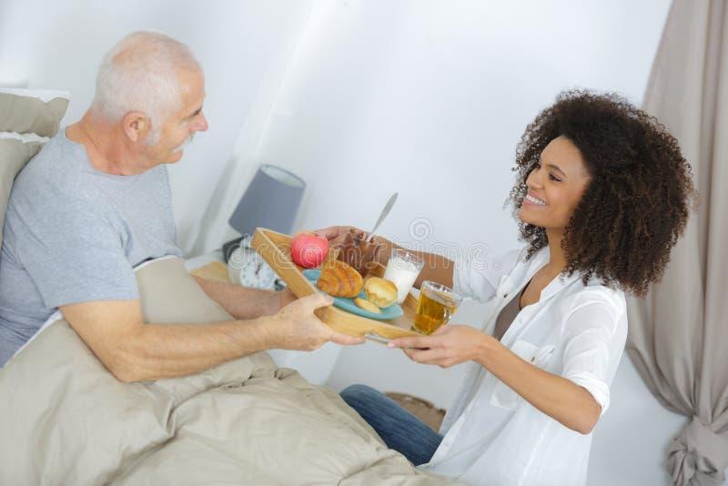 Nurse serving breakfast to senior man in bedroom stock images