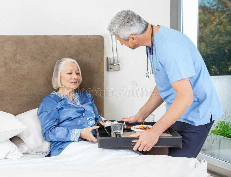 Nurse Serving Breakfast To Senior Woman On Bed stock photo