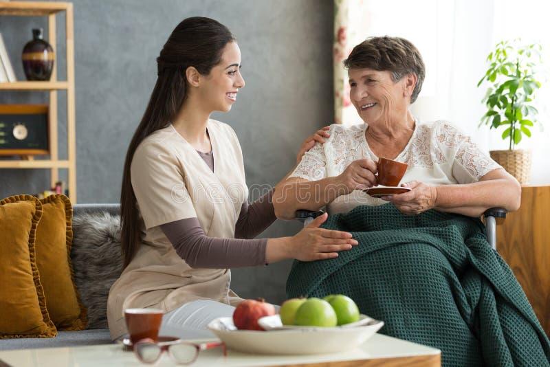 Nurse serving coffee to senior stock photos