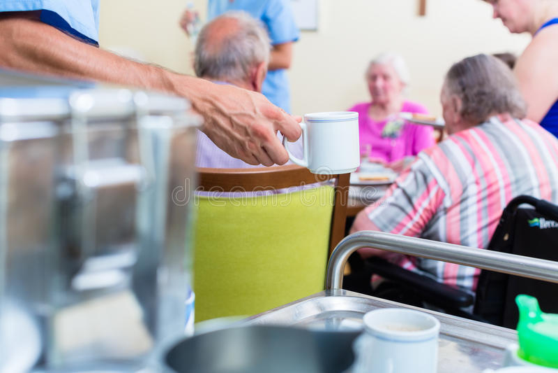 Nurse serving food in nursing home stock photography