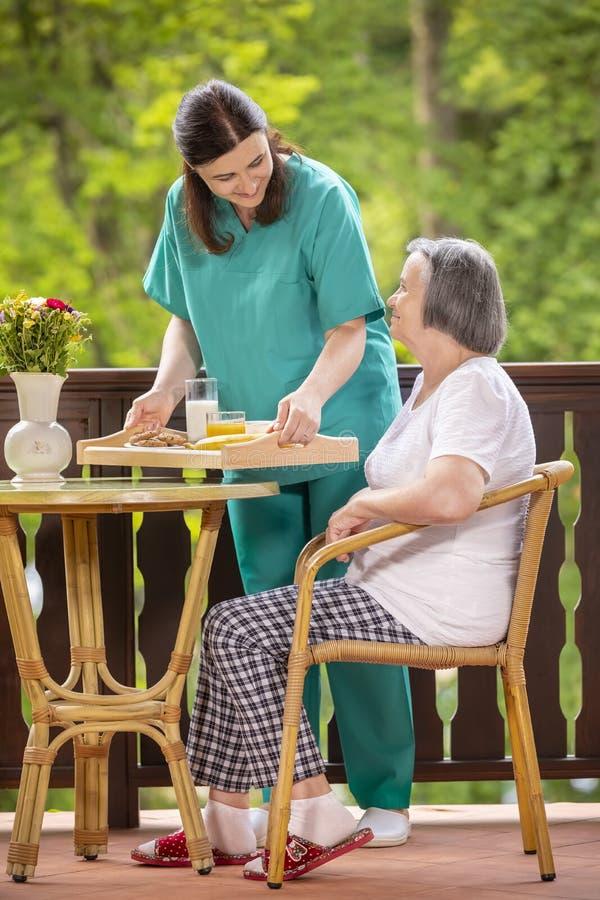 Nurse serving healthy breakfast to happy senior woman stock image