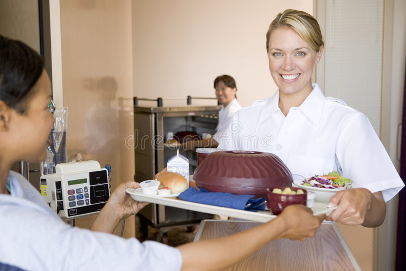 Nurse Serving A Patient A Meal In His Bed stock image