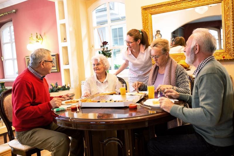 Nurse serving retirement home occupants during dinner time stock photography