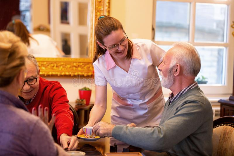 Nurse serving tea in the retirement home royalty free stock photos