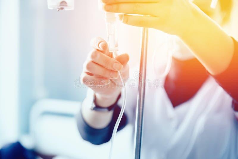 Nurse sets the patient`s dropper stock photography