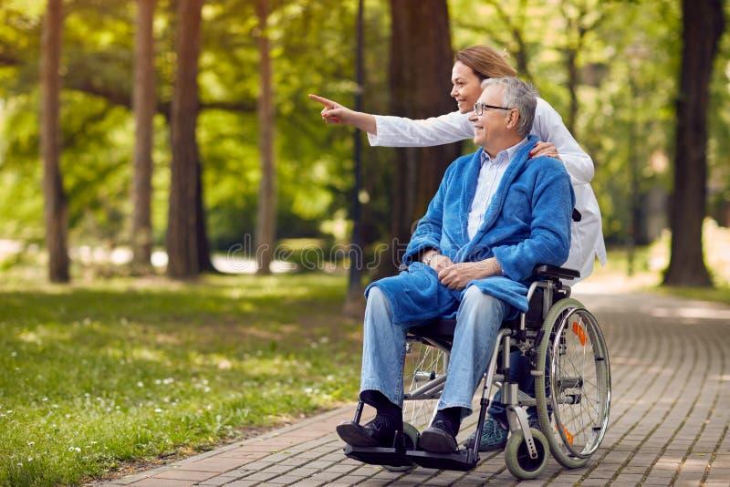Nurse showing something to elderly man on wheelchair stock images