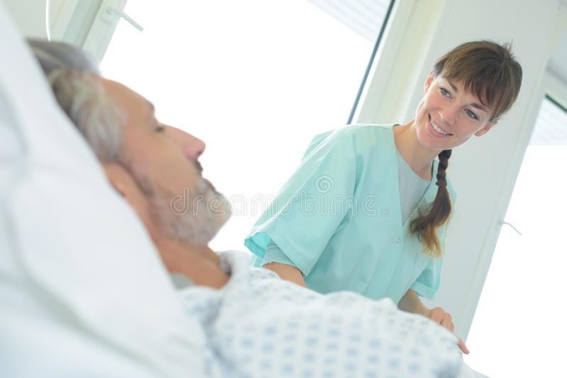 Nurse smiling at male patient royalty free stock photography