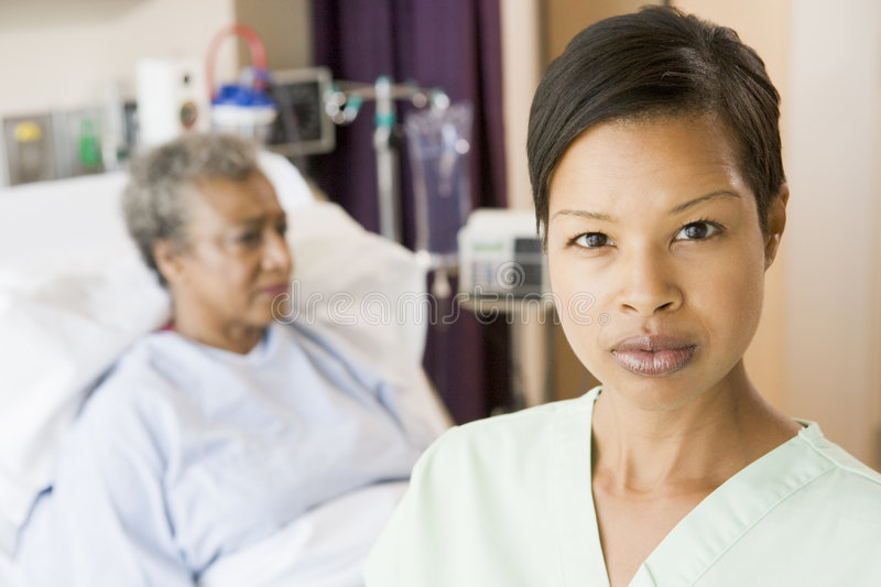 Nurse Standing In Patients Room Looking Serious. At camera royalty free stock photo