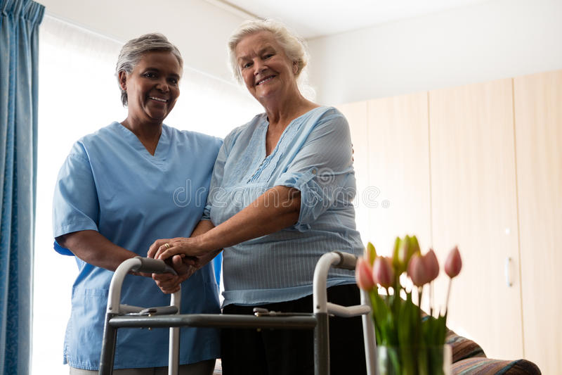 Nurse standing by senior woman holding walker in nursing home stock photo