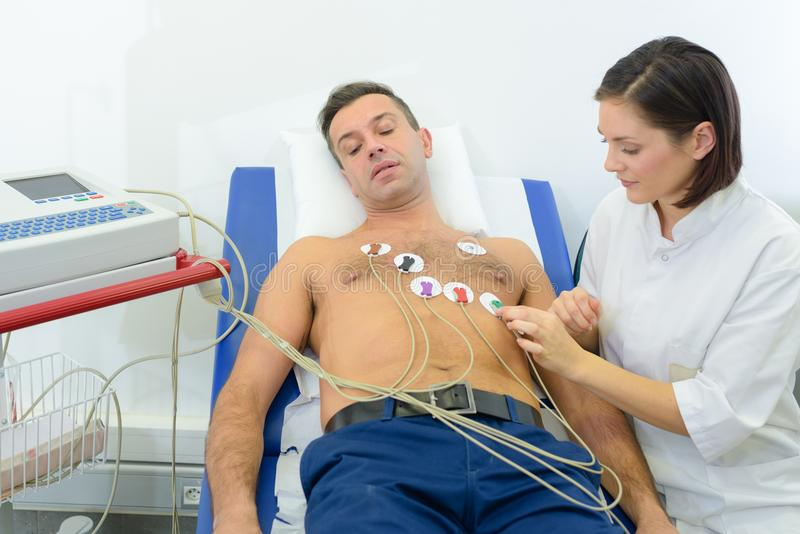 Nurse sticking heart monitor pads onto patient. Cardiac stock image