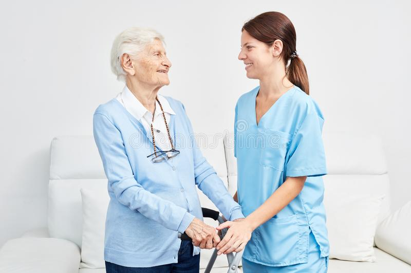 Nurse supports elderly woman with walking frame. Nurse or nursing assistant supports elderly women with walking frame in rehab royalty free stock photography