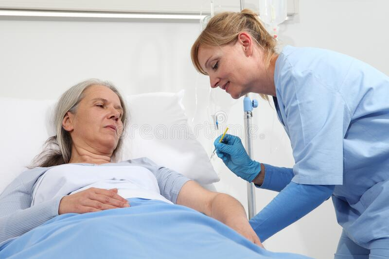Nurse with the syringe injects the vaccine to the elderly woman patient lying in the hospital room bed.  royalty free stock photos