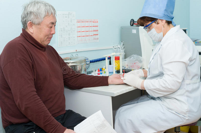 Nurse takes blood specimen for test. ULAN-UDE, RUSSIA - APRIL 6, 2010: An unidentified nurse makes blood test for volunteers before they donate blood. The City stock images