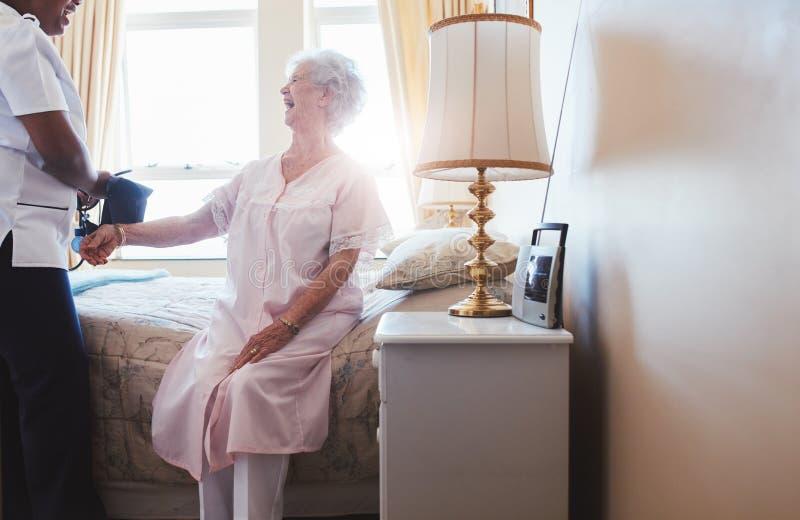 Nurse taking blood pressure of senior woman. Indoors shot of happy senior women sitting on bed with female nurse checking blood pressure. Home caregiver testing stock image
