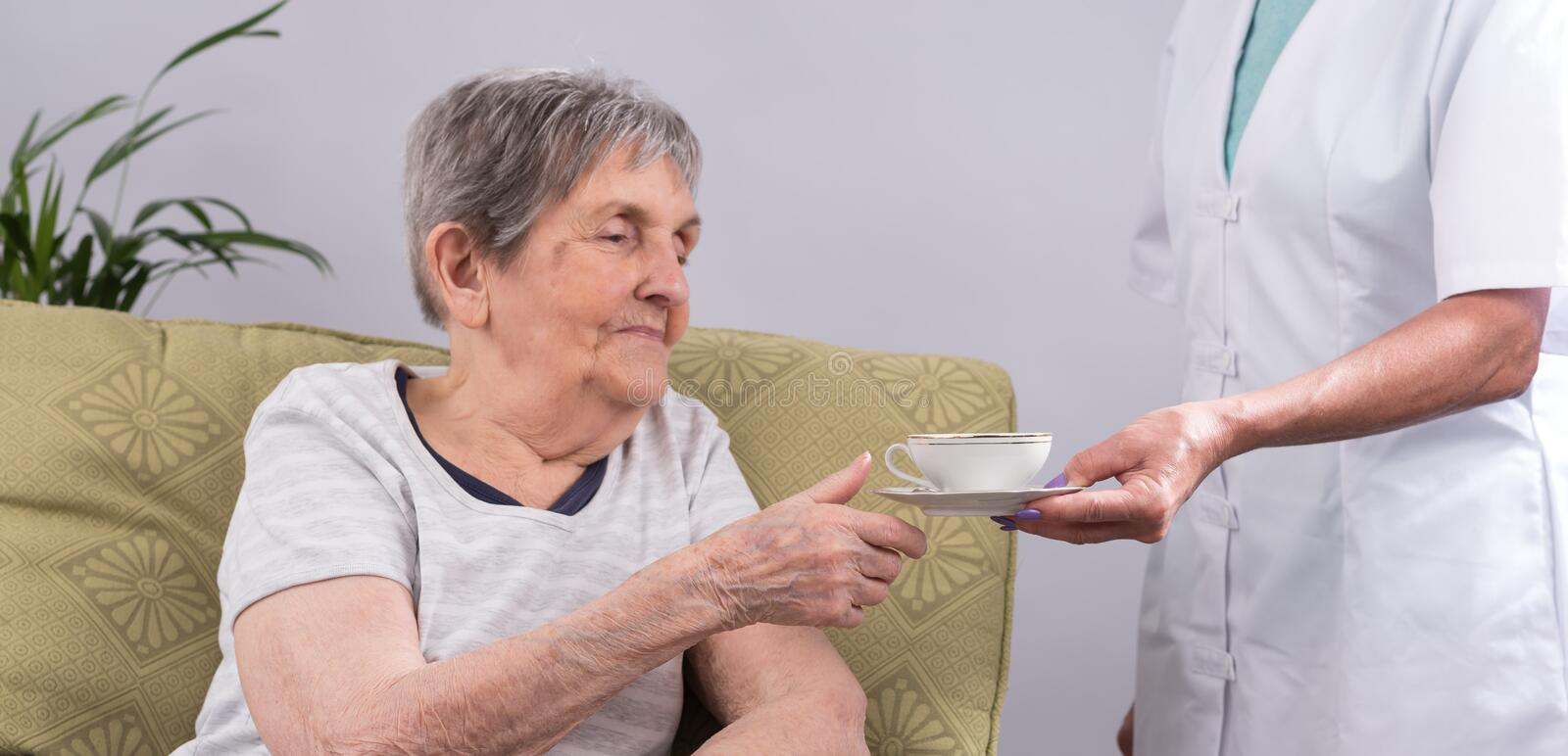 Nurse taking care of an elderly person stock images