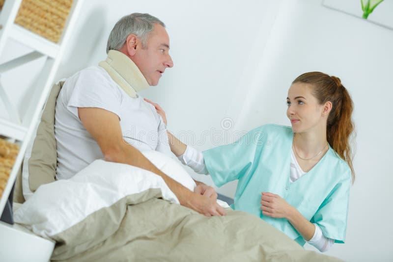 Nurse taking care injured man in bed at home. Nurse taking care of injured men in bed at home royalty free stock image