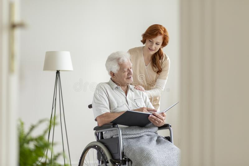 Nurse taking care of a man in a wheelchair in a nursing home. Nurse taking care of a men in a wheelchair in a nursing home concept royalty free stock images