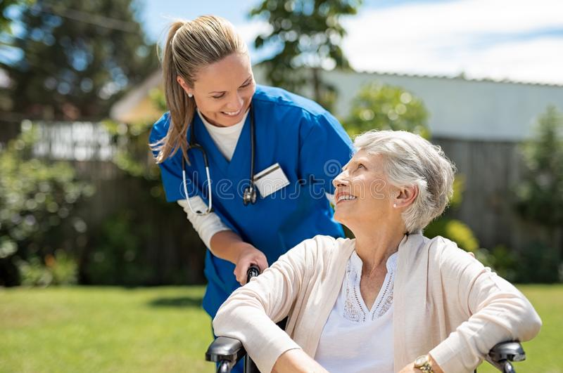 Nurse take care of senior patient. Nurse taking care of old women in wheelchair outdoor. Friendly doctor caring about elderly disabled women in wheelchair. Happy royalty free stock photography
