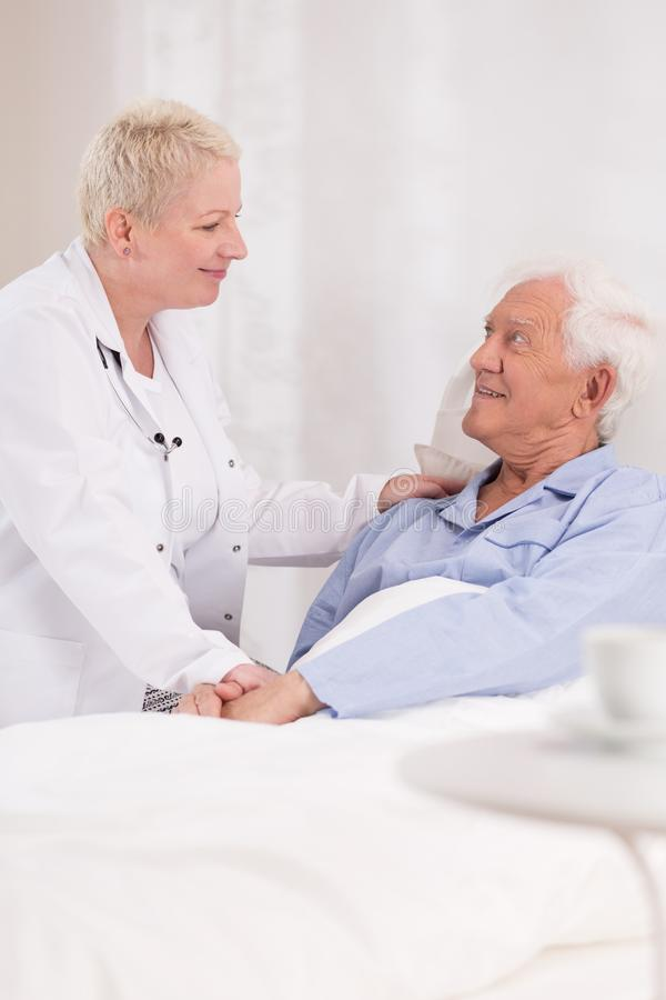 Nurse taking care about patient. Photo of mature nurse taking care about old patient stock image