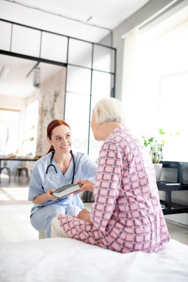 Red-haired nurse taking care of grey-haired aged woman stock image