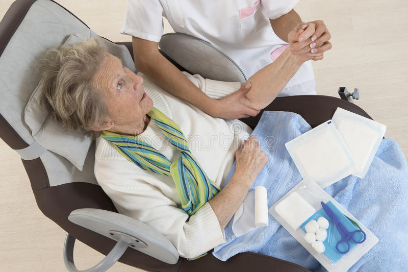 Nurse taking care of senior woman in retirement home. Bandaging her arm stock photography