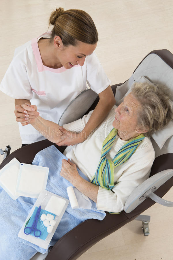 Nurse taking care of senior woman in retirement home. Nurse taking care of senior women in retirement home bandaging her arm royalty free stock image