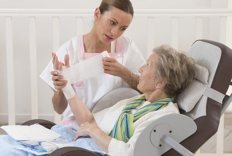 Nurse taking care of senior woman in retirement home. Nurse taking care of senior women in retirement home bandaging her arm royalty free stock photos