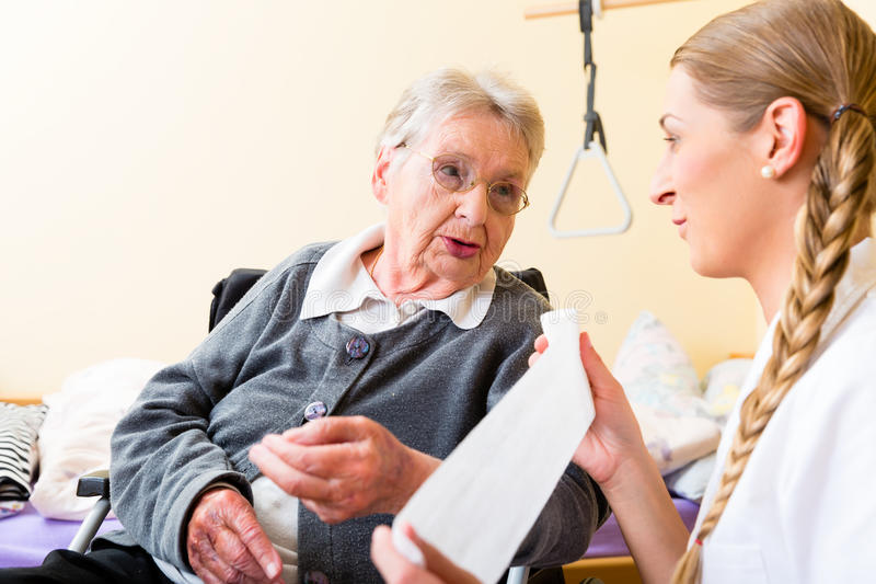 Nurse taking care of senior woman in retirement home. Nurse taking care of senior women in retirement home bandaging a wound royalty free stock photography
