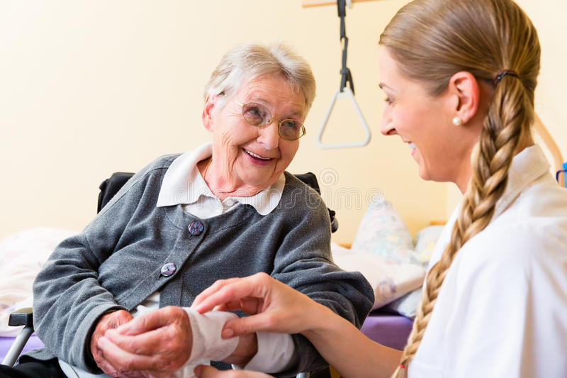 Nurse taking care of senior woman in retirement home. Nurse taking care of senior women in retirement home bandaging a wound royalty free stock image