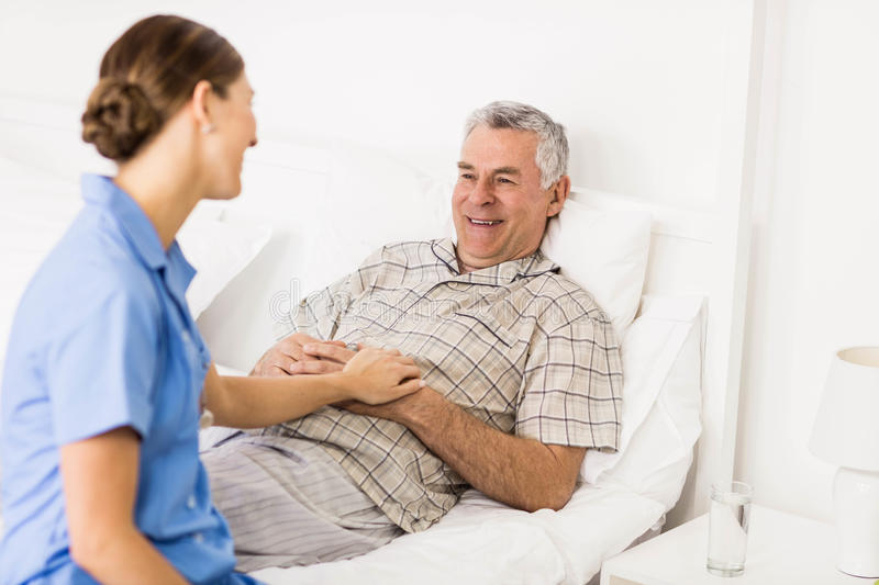 Nurse taking care of suffering senior patient stock photos