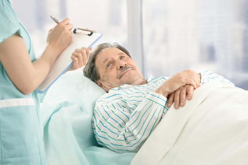 Nurse taking notes of old patient. Nurse holding clipboard, taking notes of old patient lying in hospital bed stock images