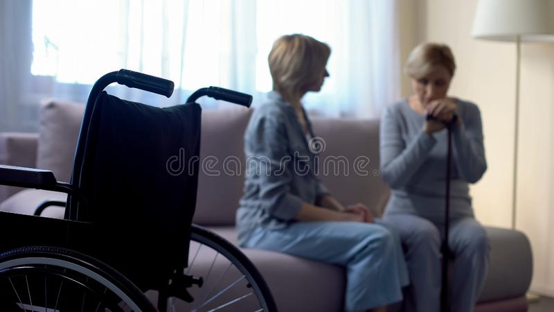 Nurse talking with depressed disabled senior woman in rehabilitation center royalty free stock photo