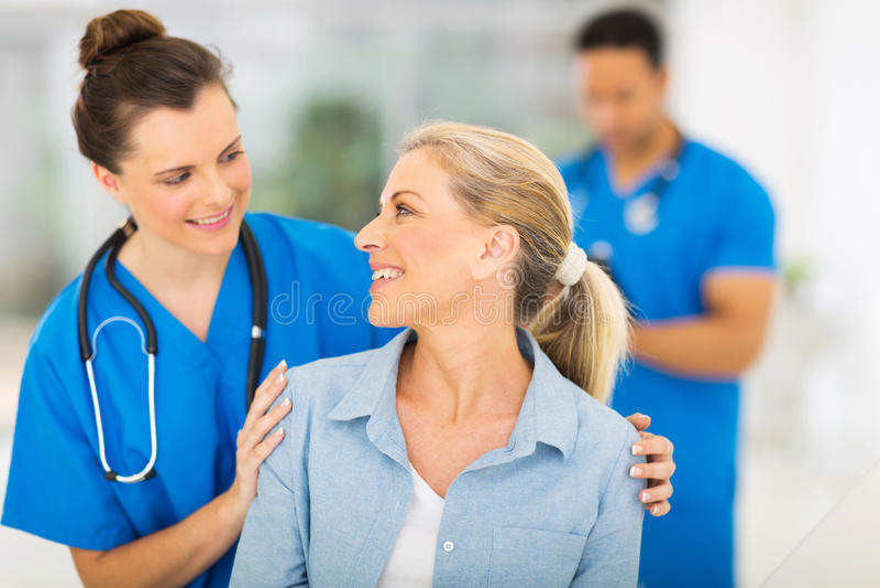 Nurse talking senior woman. Caring nurse talking to senior women in hospital royalty free stock images