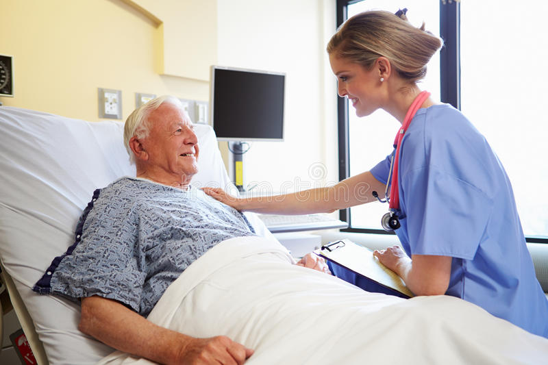 Nurse Talking To Senior Male Patient In Hospital Room. Putting Hand On Shoulder Reassuring Him stock photos